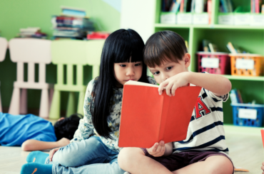 Two kindergarten students reading a book.