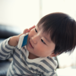 Toddler using cell phone.