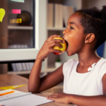 Girl eating healthy after school snack while studying.