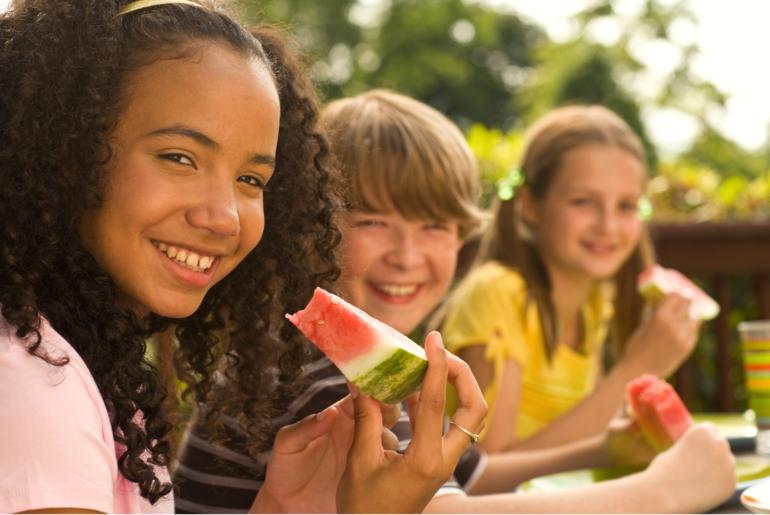 Tweens eating healthy snack of watermelon.