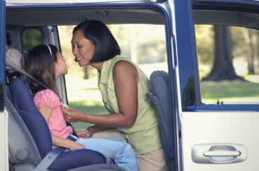 Mother strapping daughter into car seat.
