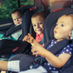 Three children buckled into a back seat.