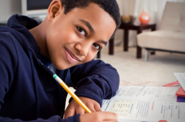 Tween smiling while doing homework.