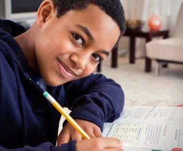 Tween smiling while doing homework.