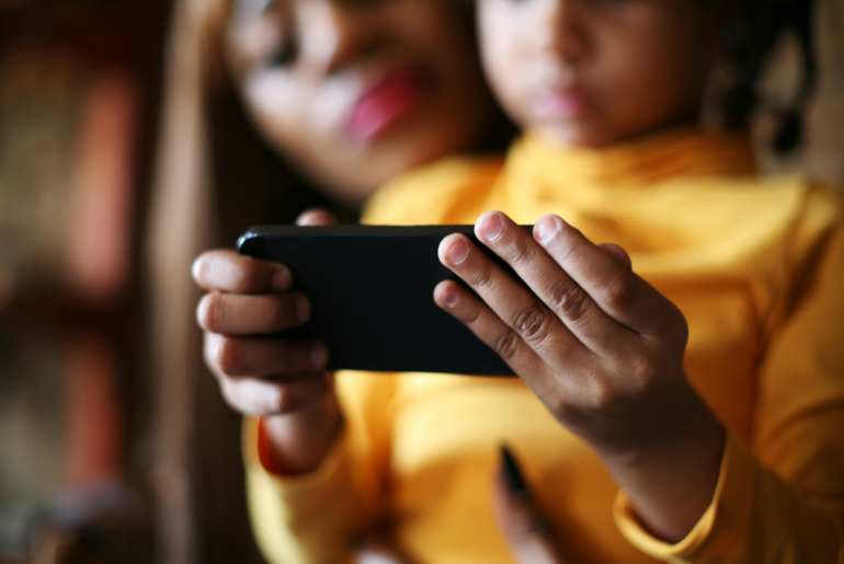 Mother and daughter looking at phone.