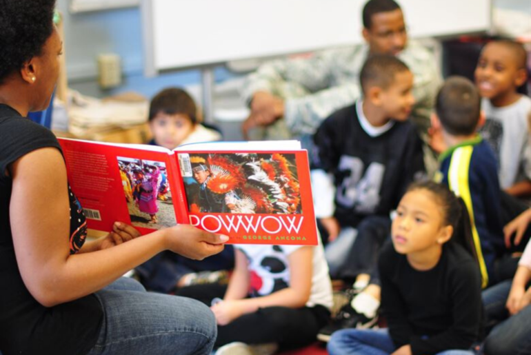 Elementary school students looking at a book about Pow Wow ceremonies.