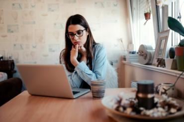 Worried woman looking at laptop.