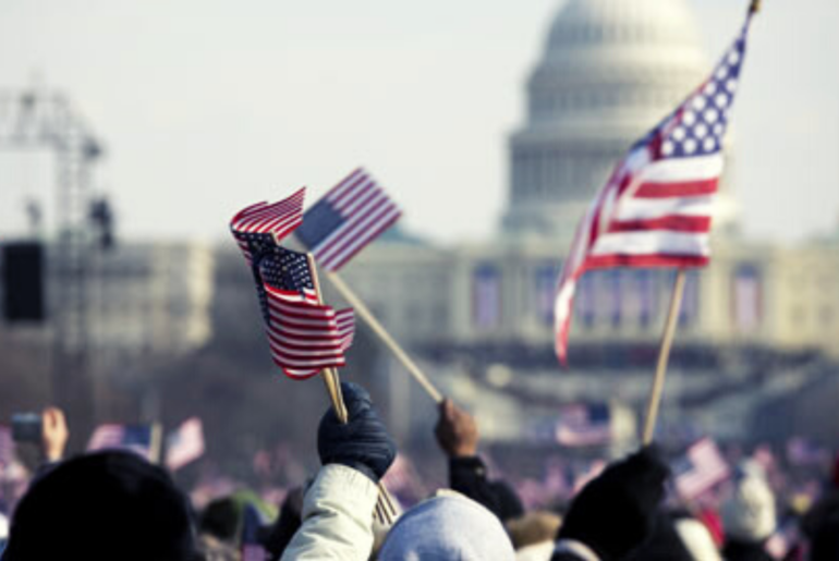 Close up of American flags waving in front of the capitol building.