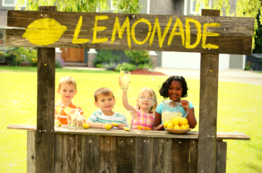 Four kids run a lemonade stand.