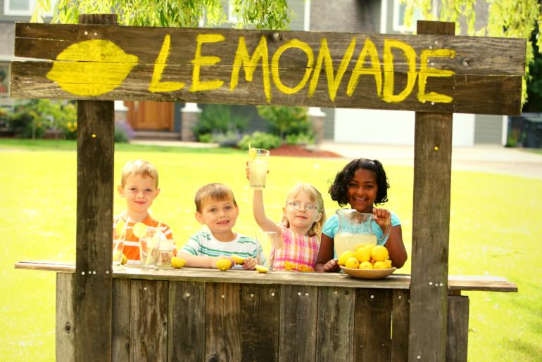 Four kids run a lemonade stand.