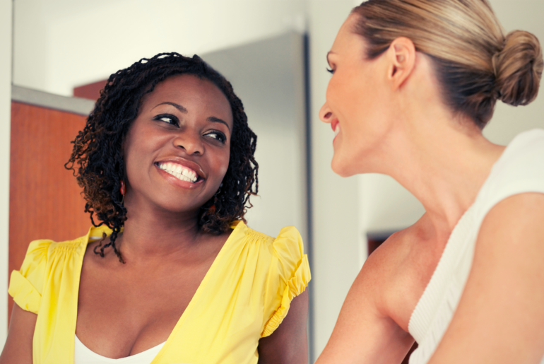 Two women smiling and talking.
