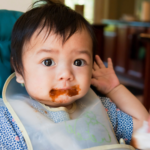 Messy baby eating solid food.