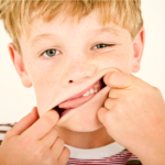 Boy touching his face with his fingers in his mouth.