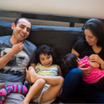 Family laughing on the couch.