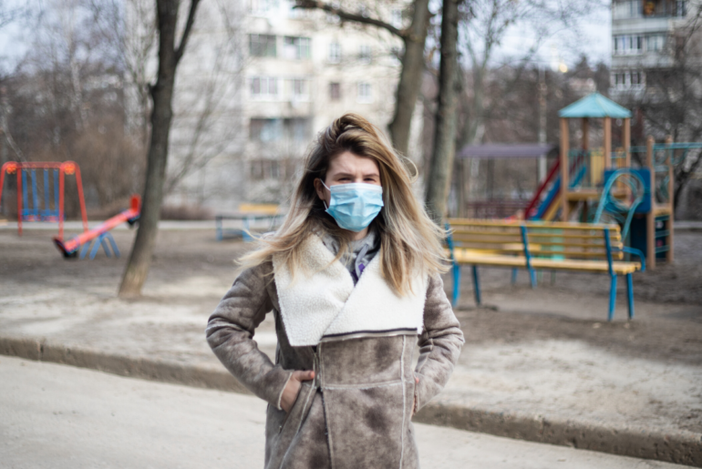 Woman wearing face mask walking by empty playground.