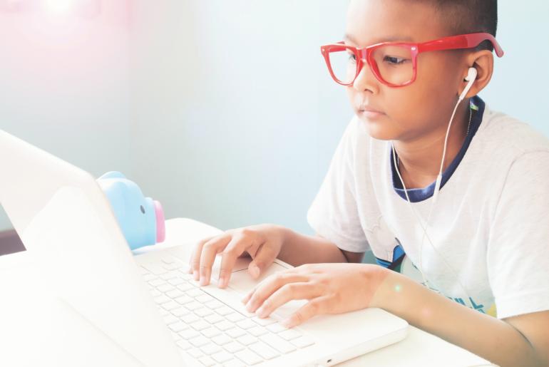Boy using computer with headphones.