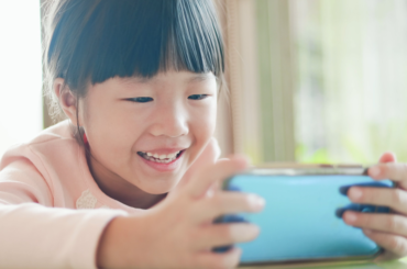 Young girl smiling during a video chat.