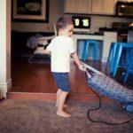 Boy using vaccum cleaner.