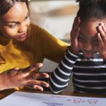 Mother helping frustrated daughter with school work.