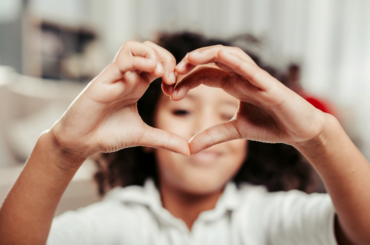 Child making heart with hands.