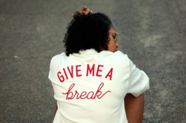 "Woman with her back to the camera wearing a shirt that says ""Give me a break."""