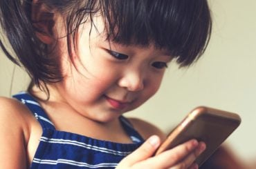 Little girl using handheld device.