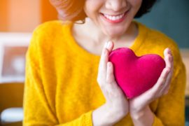Smiling woman holding plush heart.