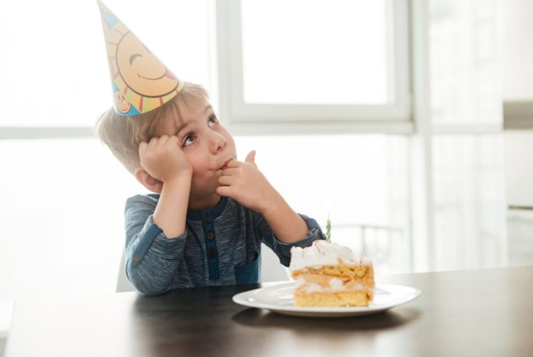 Boy tasting some frosting from his birthday cake.