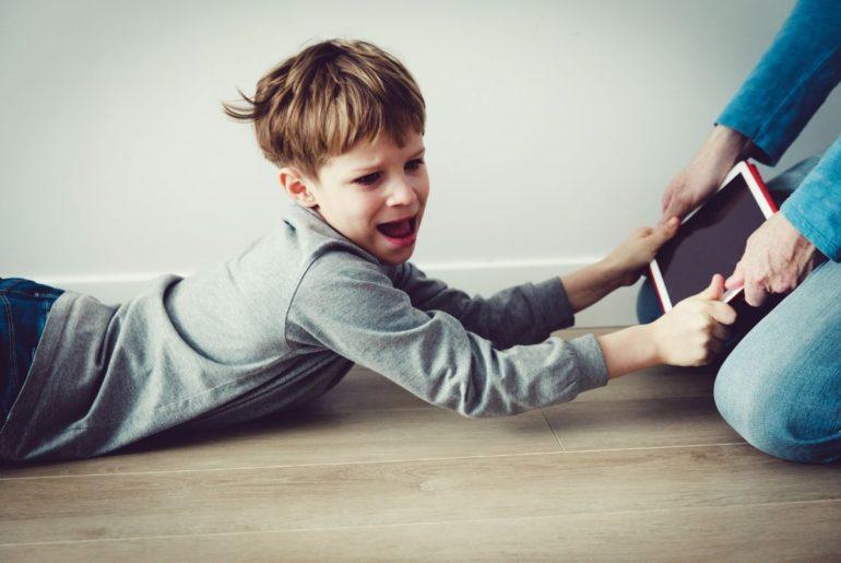 Boy having meltdown over tablet.