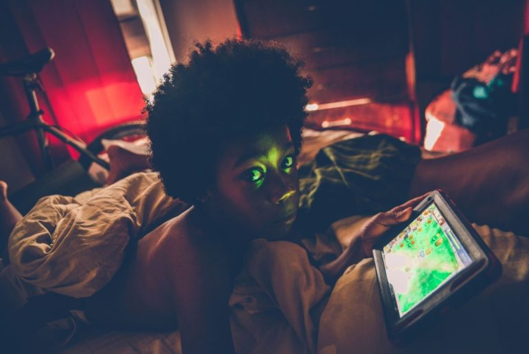 Child using device in bed.