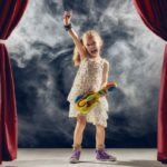 LIttle girl on stage with a toy guitar.