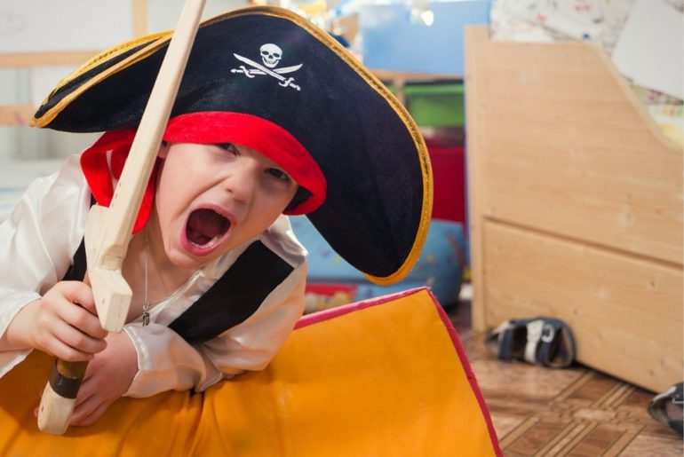 Boy dressed up as a pirate playing for the camera.