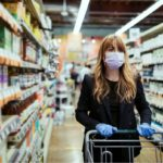Woman shopping in grocery store wearing face mask.