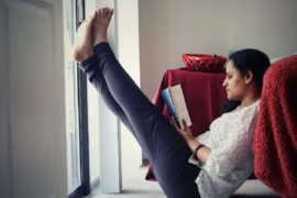 Woman with her feet up reading at home.