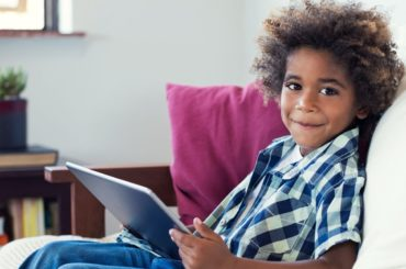 Boy looking away from tablet smiling.
