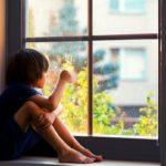 Lonely boy sitting in window sill.
