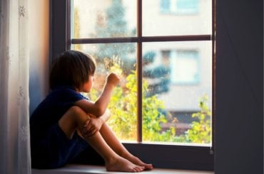 Lonely boy sitting in window sill.