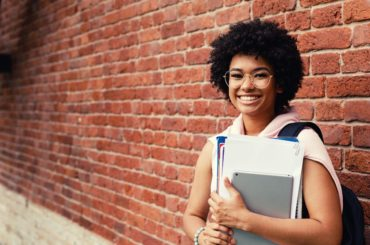Smiling teen student with brick background.