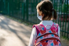 Little girl wearing facemask and a backpack to school.