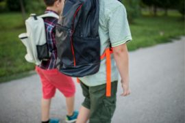 Two boys walking to school with backpacks.