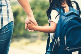 Child wearing backpack holds parent's hand.