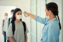 Students having temperature taken at school.