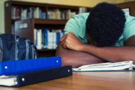 Frustrated student without laptop with his head in his arms.