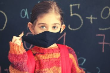 Girl taking her mask off at school.