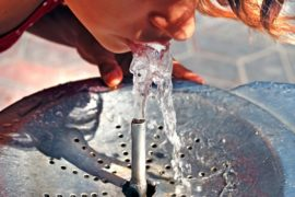 Child drinking from a water fountain.