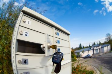 Condominium mailboxes with one of them open.