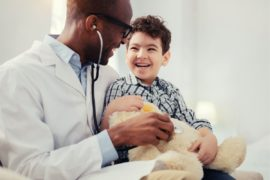 Boy laughing with pediatrician.