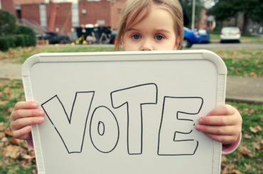 "Girl holding sign that says ""Vote."""