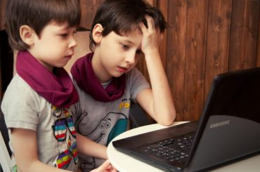 Two boys using laptop.