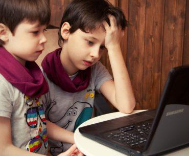 Two boys using laptop.